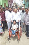 Rajendra Darda providing wheelchair to handicapped persons.